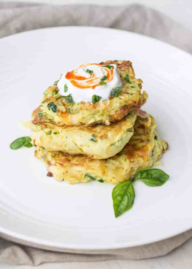 Zucchini & Eggs Breakfast Fritters on a plate topped with sourcream, and basil.