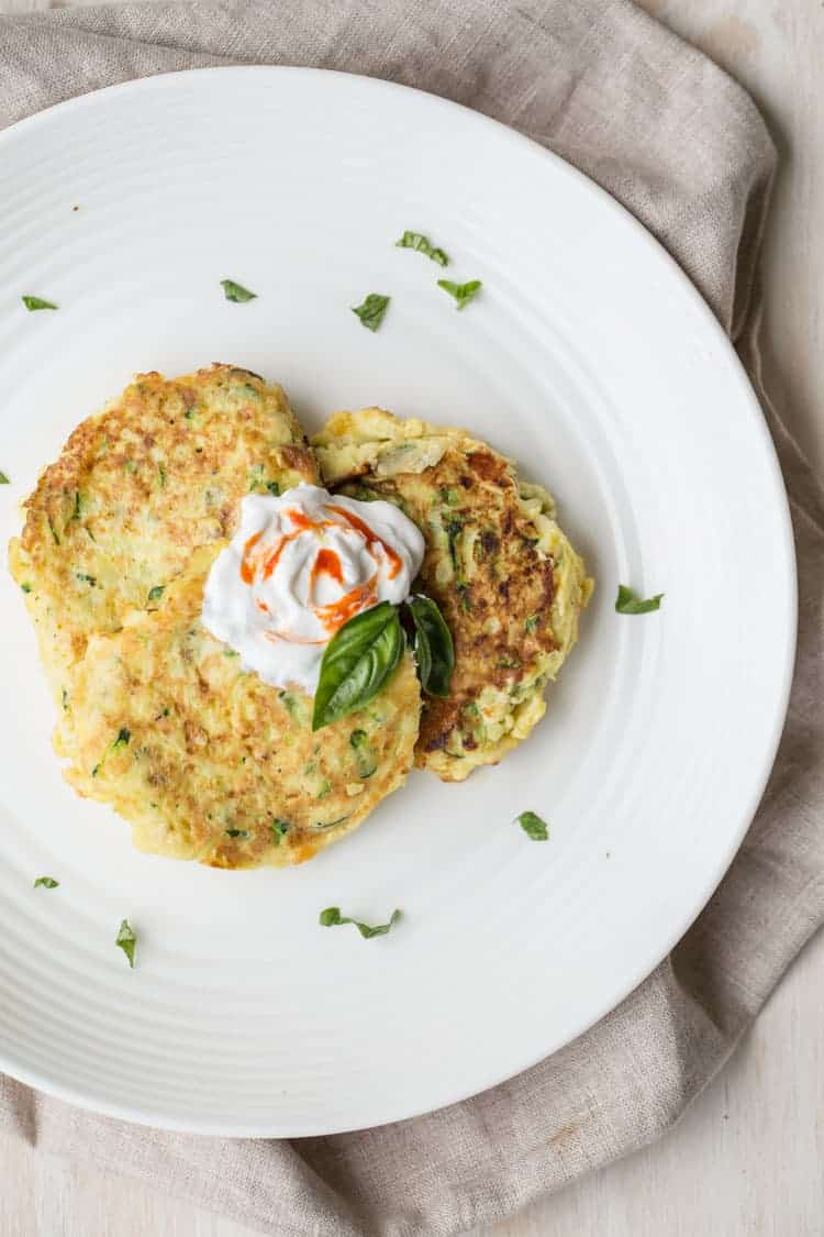 Three egg zucchini fritters on a plate with sourcream and sriracha on top with chopped basil.