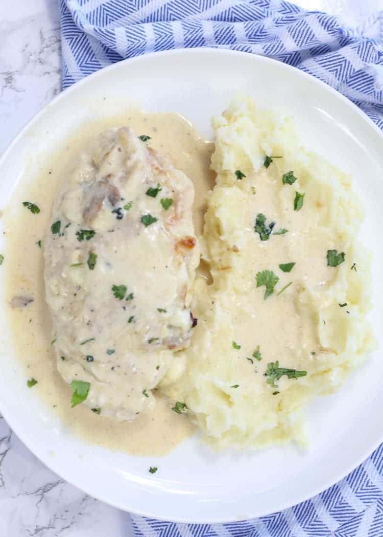 Mushroom stuffed chicken on a plate with mashed potatoes.