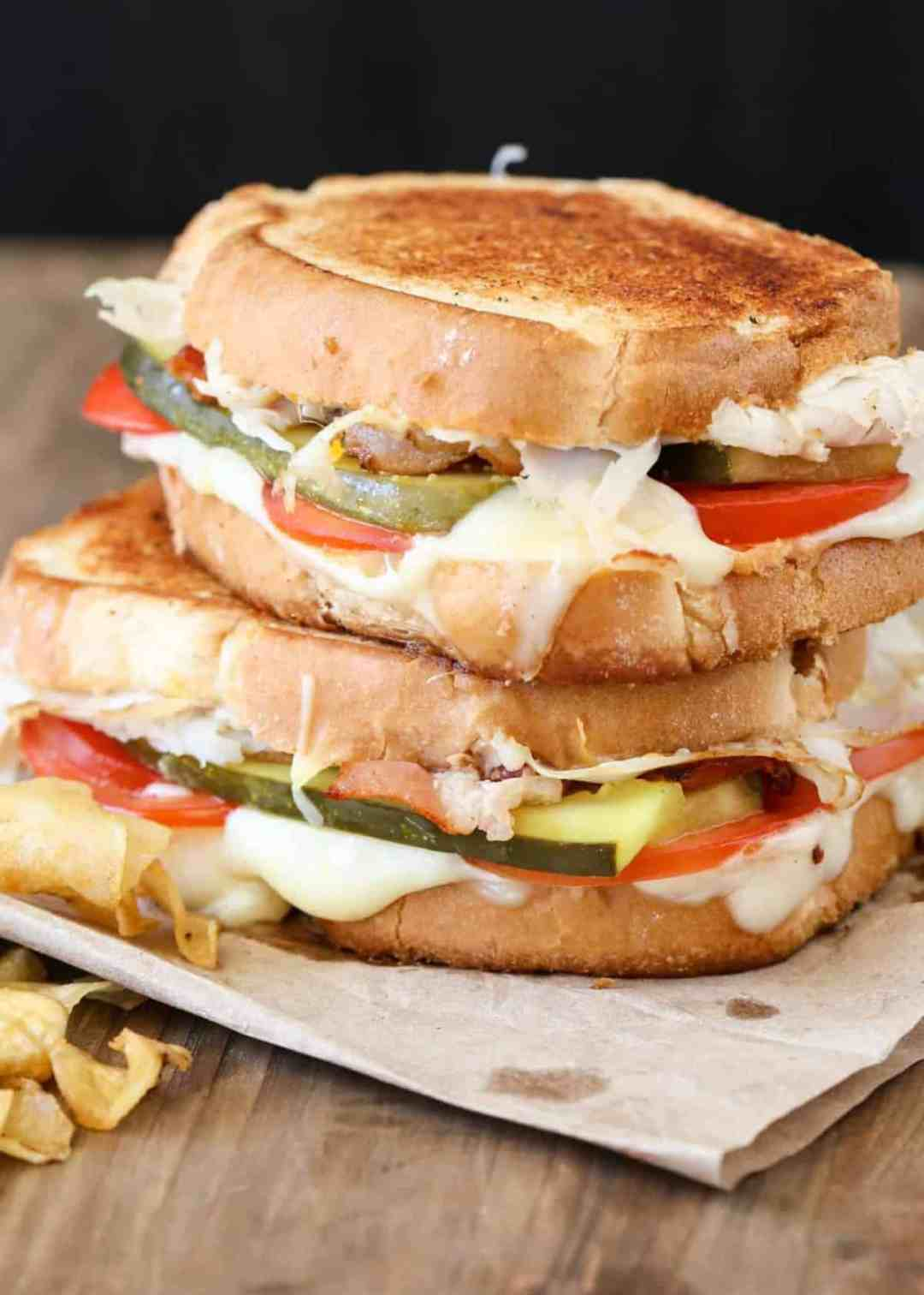 Turkey bacon grilled cheese recipe with two sandwiches stacked ontop with chips.