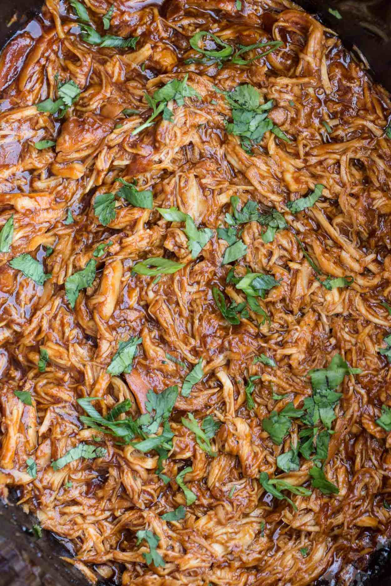 BBQ pulled chicken crock pot recipe topped with fresh greens in a slow cooker.
