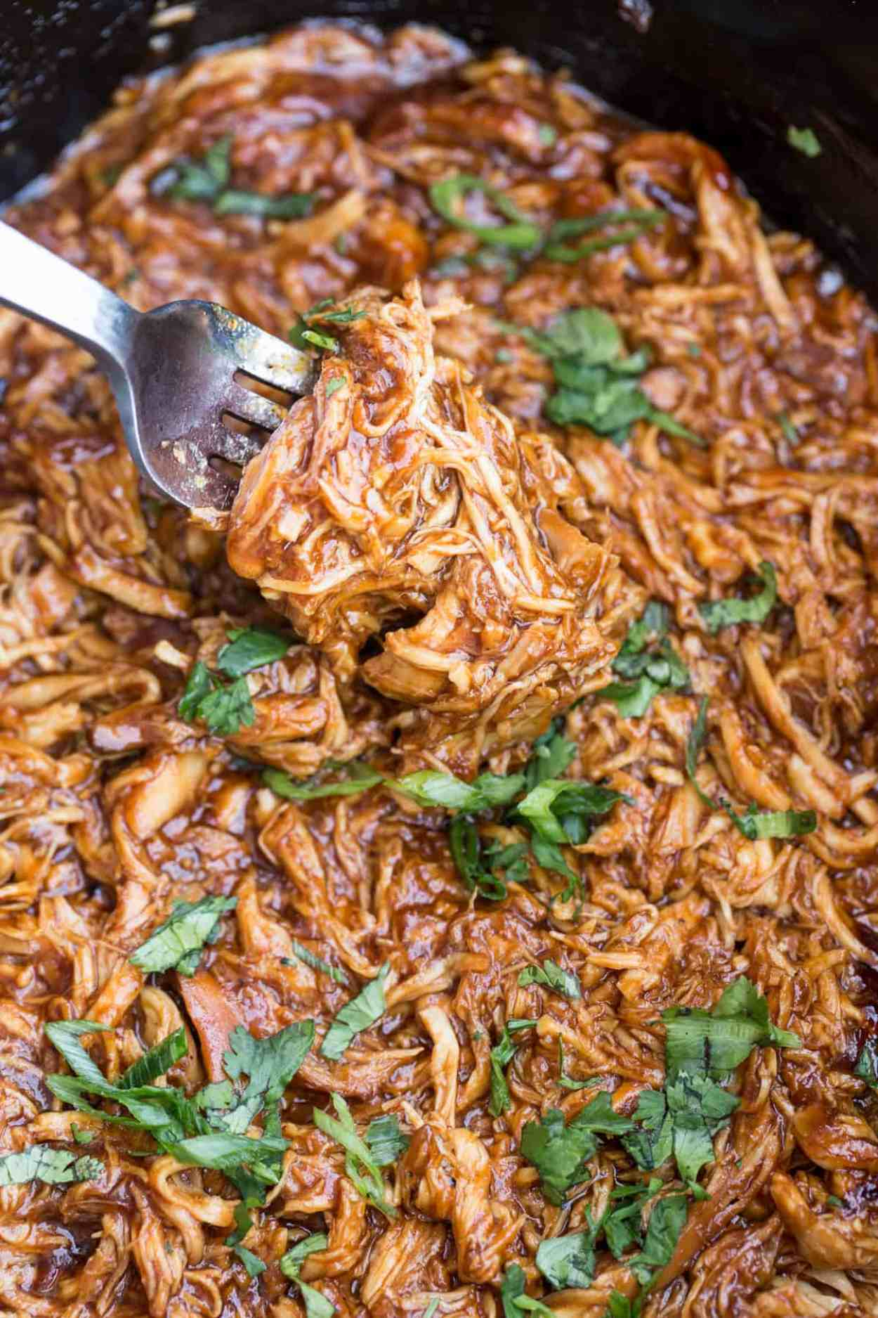 BBQ pulled chicken in a crock pot with a pork topped with fresh greens.