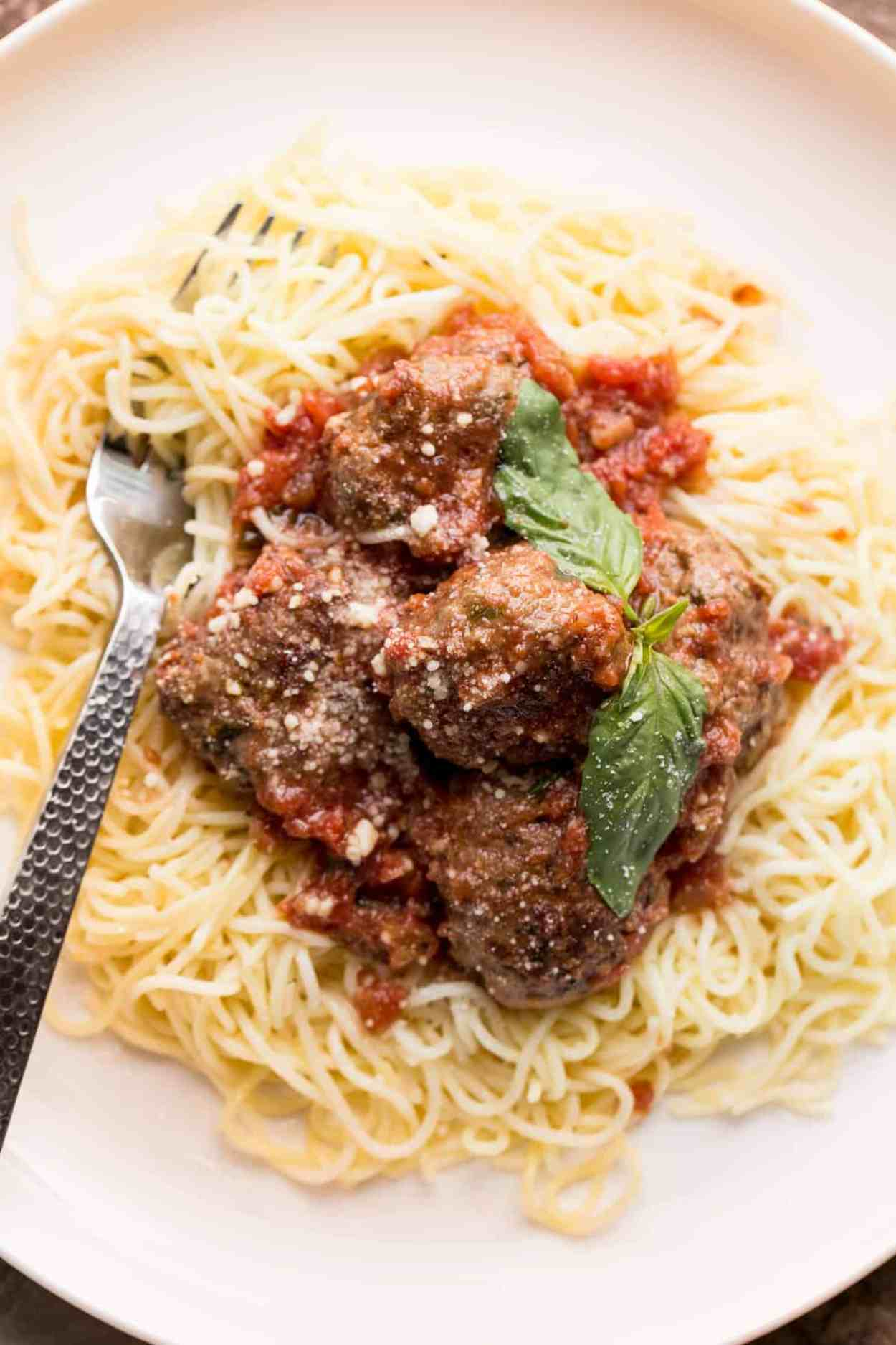 Easy meatball recipe topped with a homemade meatball sauce. Served with pasta on a plate.