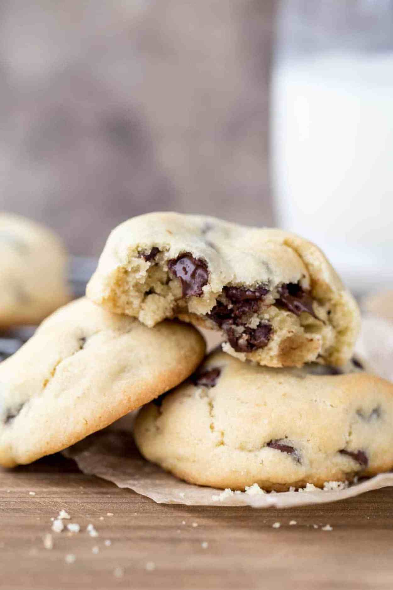 Chocolate chip cookies stacked on top of each other with chocolate chip morsels.