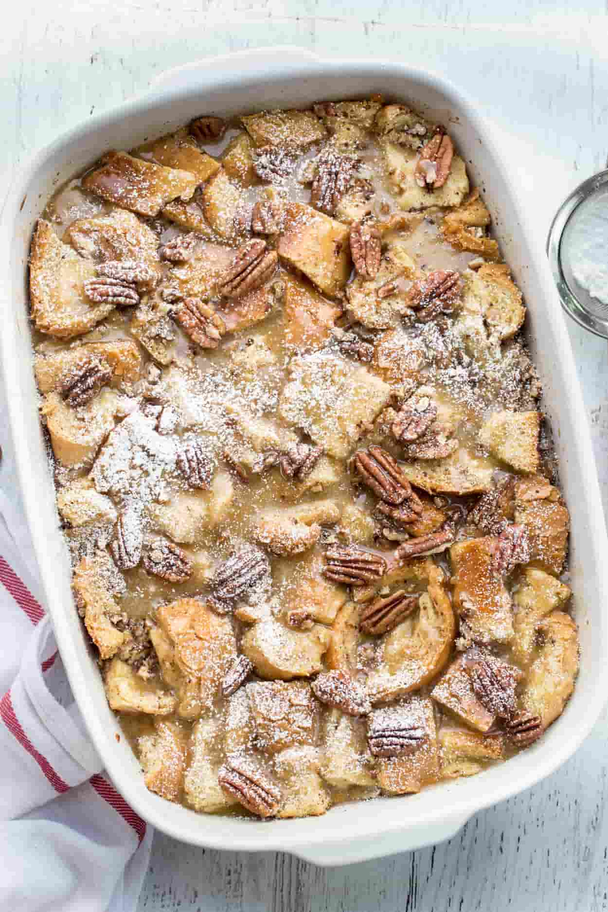 Maple pecan french toast casserole recipe with pecans and topped with powdered sugar.