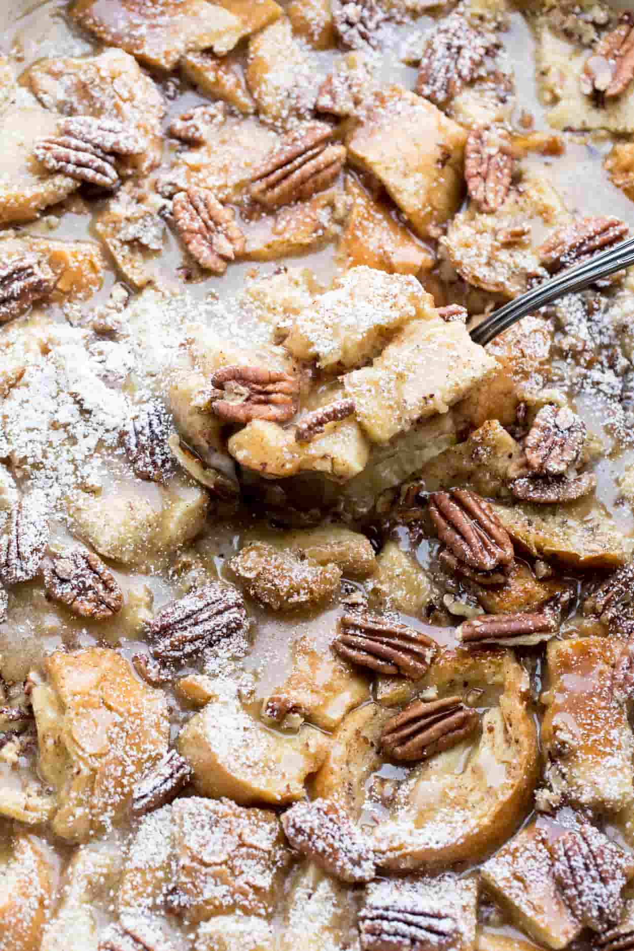 Upclose picture of this maple pecan french toast casserole with a spoon and topped with powdered sugar.
