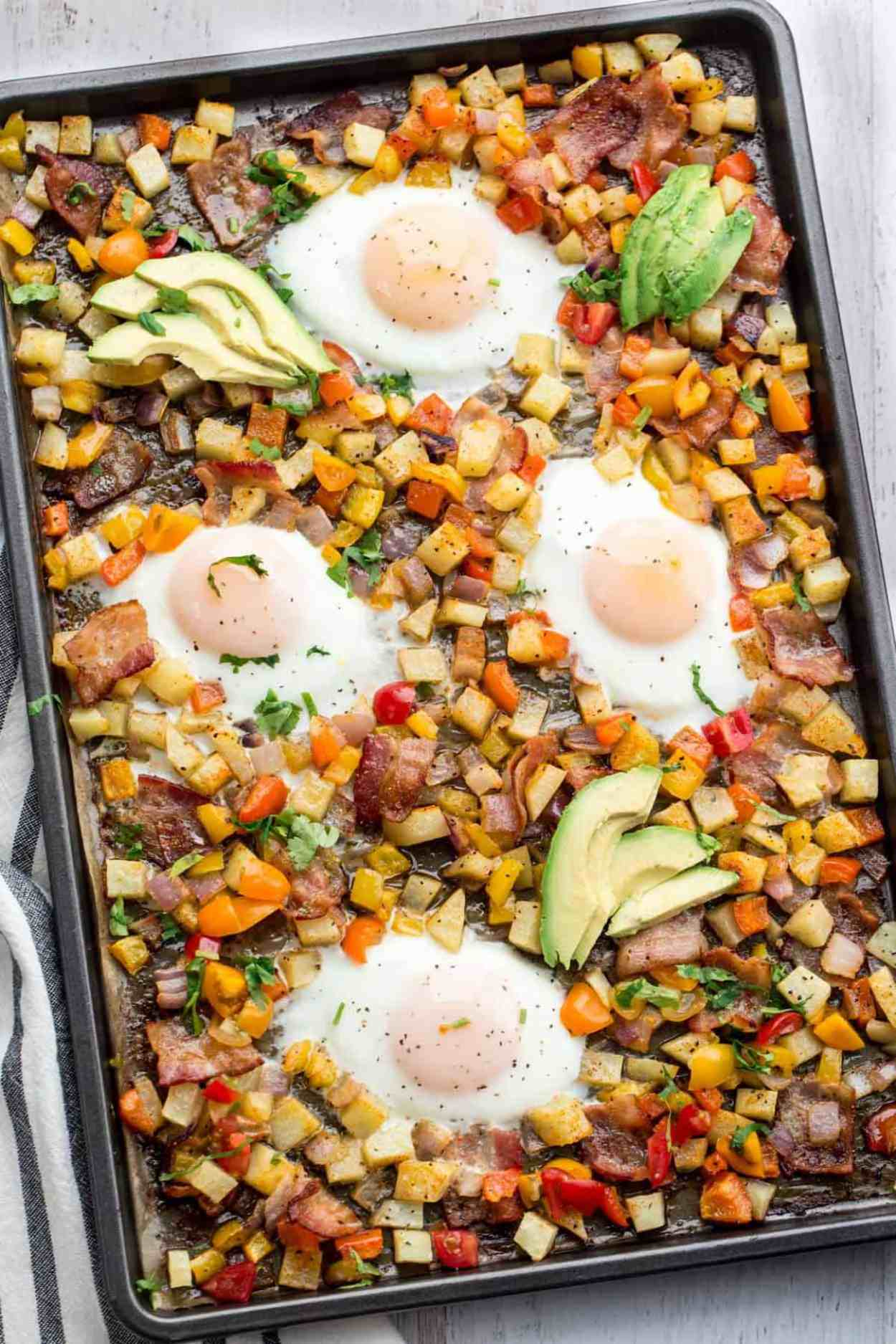 One pan breakfast potatoes and eggs with vegetables and bacon.