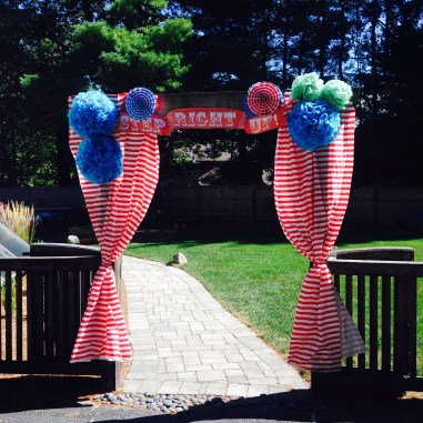 The yard entrance..i used striped tablecloths from Target and hand made pom poms