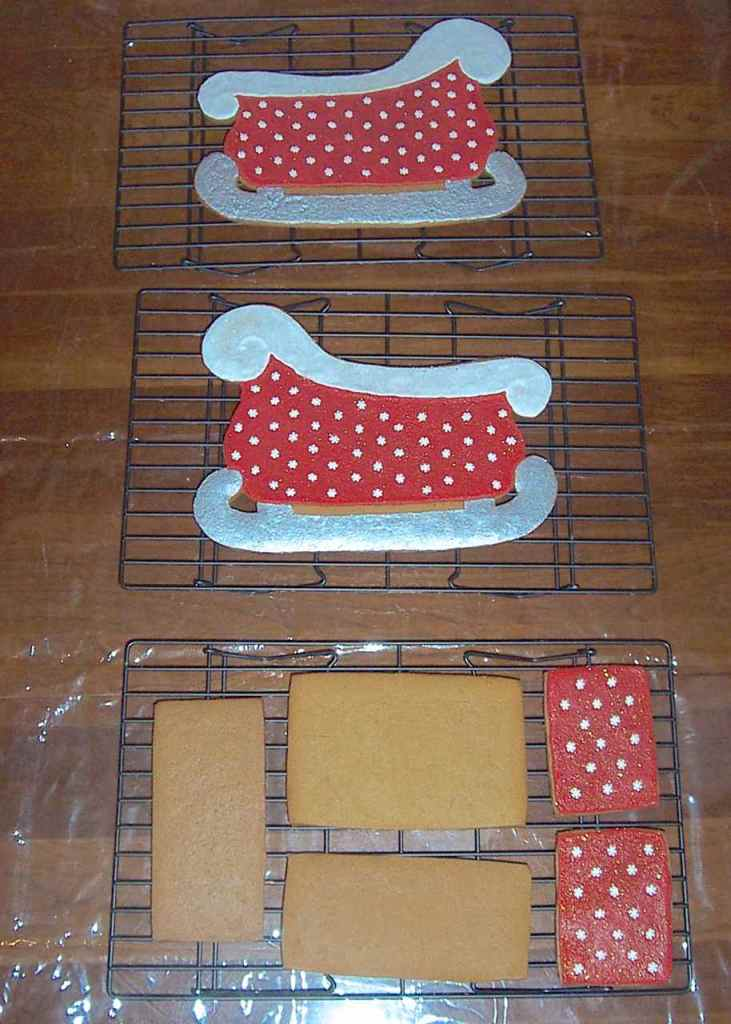 """All the unassembled pieces of the sleigh - iced and un-iced - two sides, four """"box"""" pieces laid out on racks to dry."""