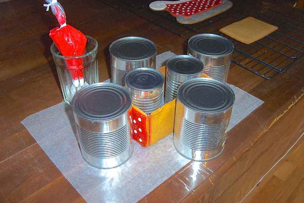 "Side view of the cans holding up and holding together the glued sides of the sleigh ""box"" for drying."