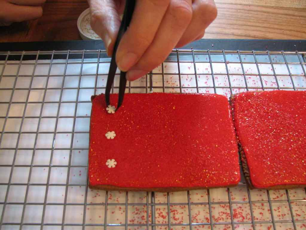 Sugar snowflakes being added with a tweezer to the still-wet, flooded and sugared box panels.