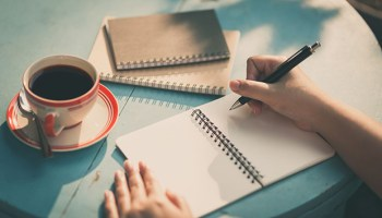 A hand writing in a blank notebook.