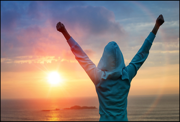 A woman triumphantly standing before a sunrise.