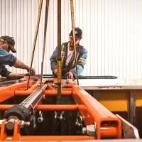 Two Valid team members building on trailer auto tarp.