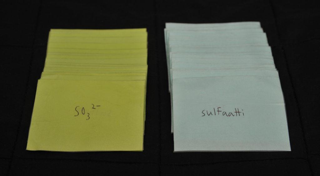 """Vihreiden korttien pino, jonka päällimmäisessä kortissa lukee """"SO32−"""", ja sinisten korttien pino, jonka päällimäisessä kortissa lukee """"sulfaatti""""."""