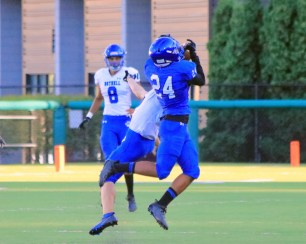 Kyree Percival (blue) goes for the catch