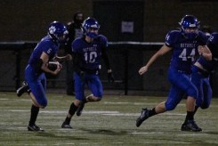 Peter Cecil and Tyson Hoke blocking as Bryce Kooy carries