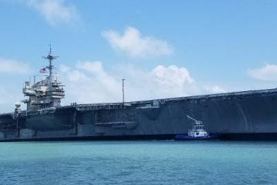 The decommissioned aircraft carrier USS Independence receives a tow through the Brownsville Ship Channel June 1, on her way to International Shipbreaking Ltd's yard at the Port of Brownsville.