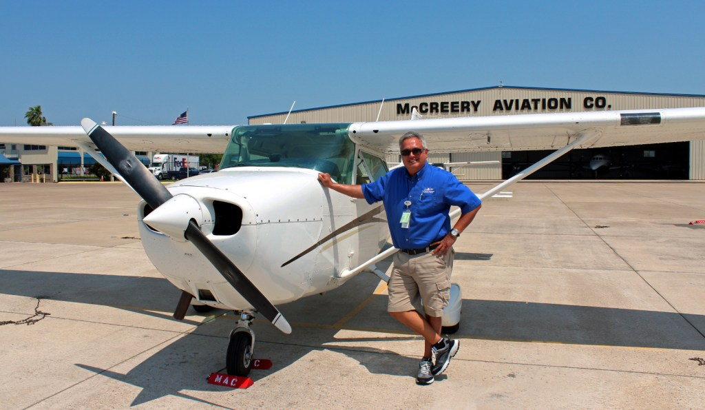 Chief flight instructor Mike Garza stands next to one of the airplanes used for student flying lessons. (VBR)