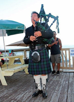Grady Buntin plays Taps with a bagpipe right before sunset on the deck of Lobo Del Mar. (VBR)