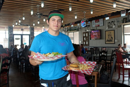 Spanky's server Paul Torres delivers a couple of burgers to customers. (VBR)