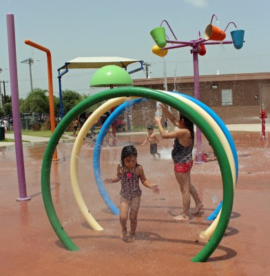 A girl dashes through cool mist spewing from a feature at the Freddy Gonzalez Memorial Park splash pad. (VBR)