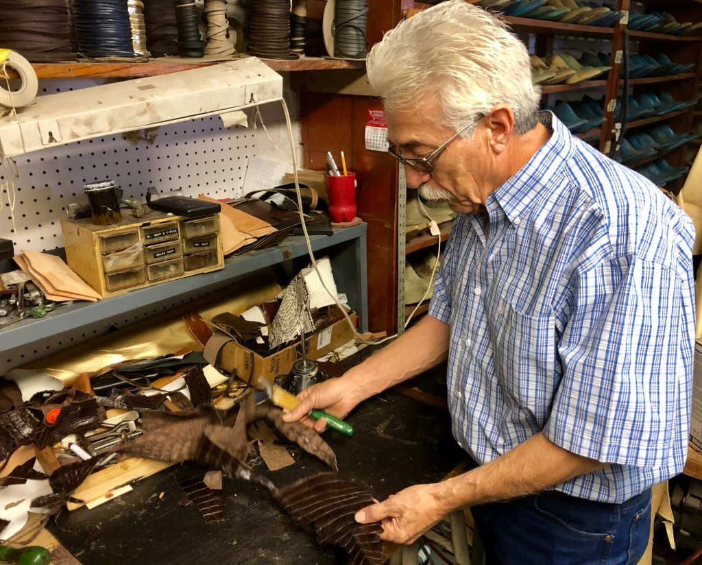 Henry Camargo in his shop working over leathers.