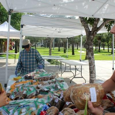 Rebecca de la Garza buys a specialty bread from April Kminiak of Frannys' Garden of Bayview at the Brownsville farmers market.