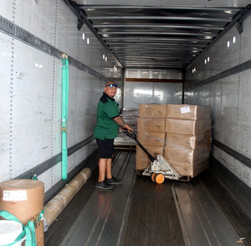 A company driver load boxes with merchandise into an eighteen wheeler for delivery.