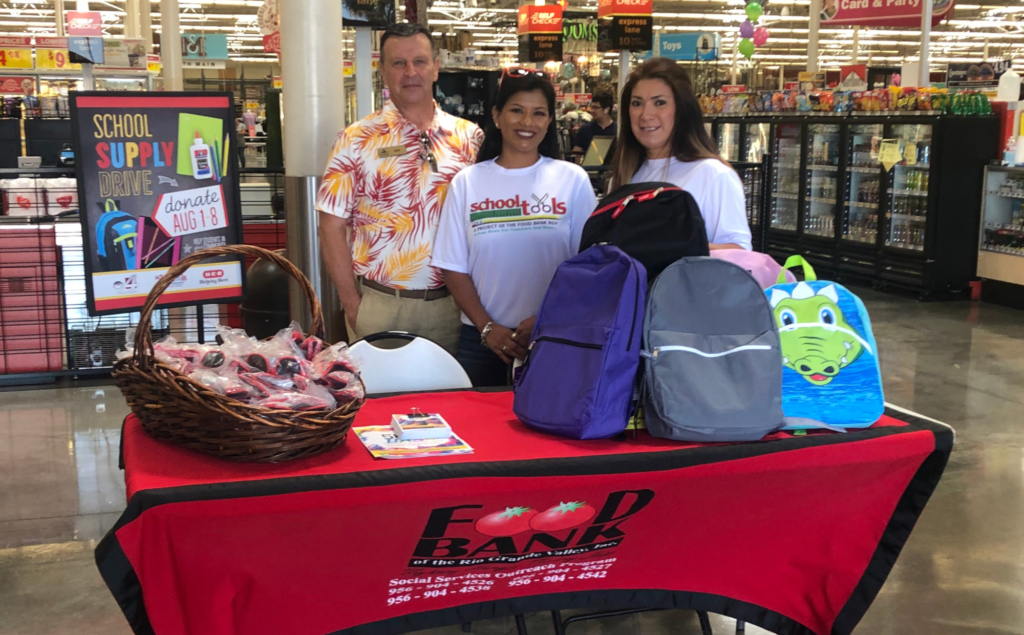 """Setting up """"Fill the Bus"""" are Mike Bigelow of Schlitterbahn, School Tools manager Erica Lechuga and RGV Food Bank Agency Referral Specialist Lynda Galvan."""