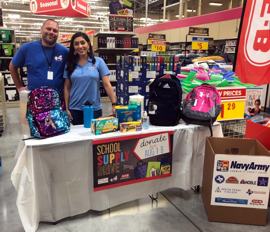 """Channel 4 reps Richard Vickes and Clara Benitez set up for on-air updates of the """"Fill the Bus"""" event."""