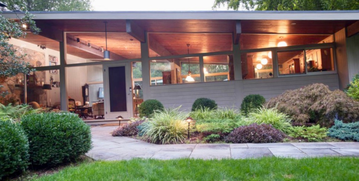 This mid-century modern home is classic with a number of elongated windows and plentiful vegetation.