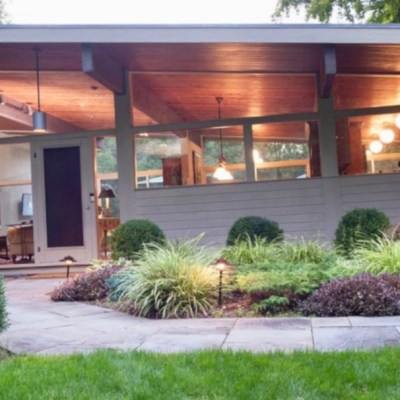 a mid-century modern home, a classic one, lots of windows, elongated, lots of vegetation in its surroundings.