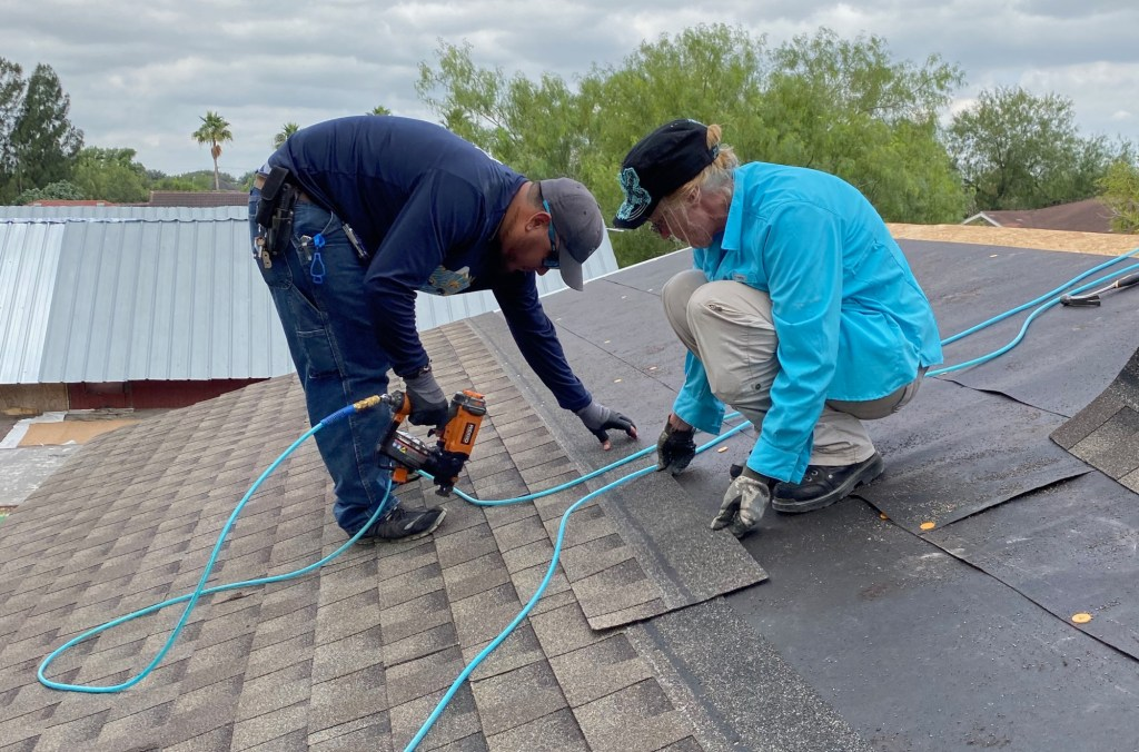 Two volunteers lay shingles on a new home build. (VBR)