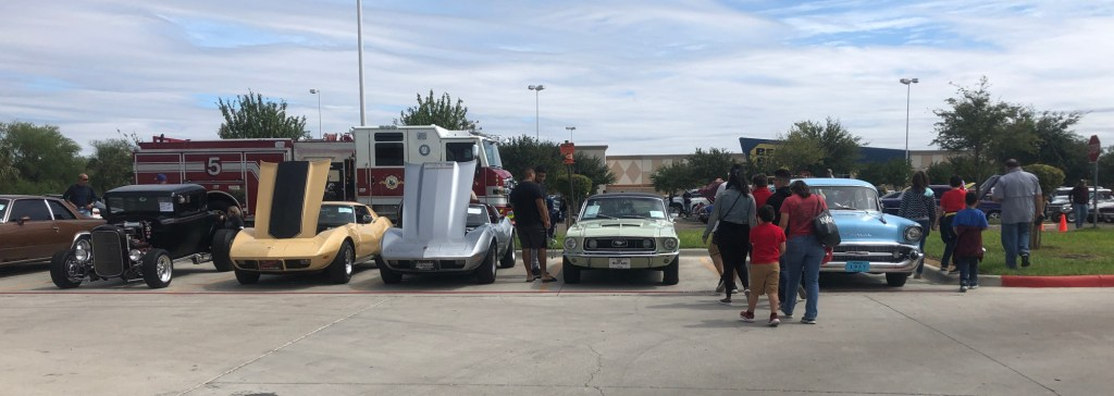 A diverse car lineup with a McAllen fire truck on display.