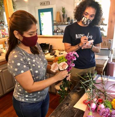 Alan Rodriguez writes in an order while his mother, Mariana Linaldi-Rodriguez, arranges a floral set for a customer.