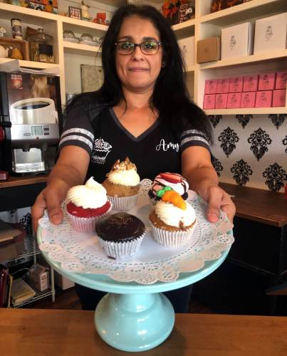 Amy de la Pena Houston displays some of her colorful cupcakes.