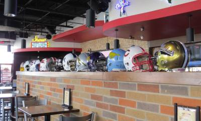 Football helmets from local high schools serve as colorful accessories at Wing Zone Grill & Tap.