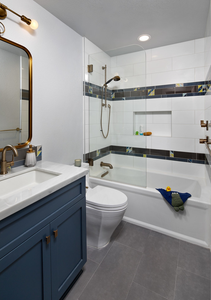 A bathroom with navy blue cabinets and a tile shower.
