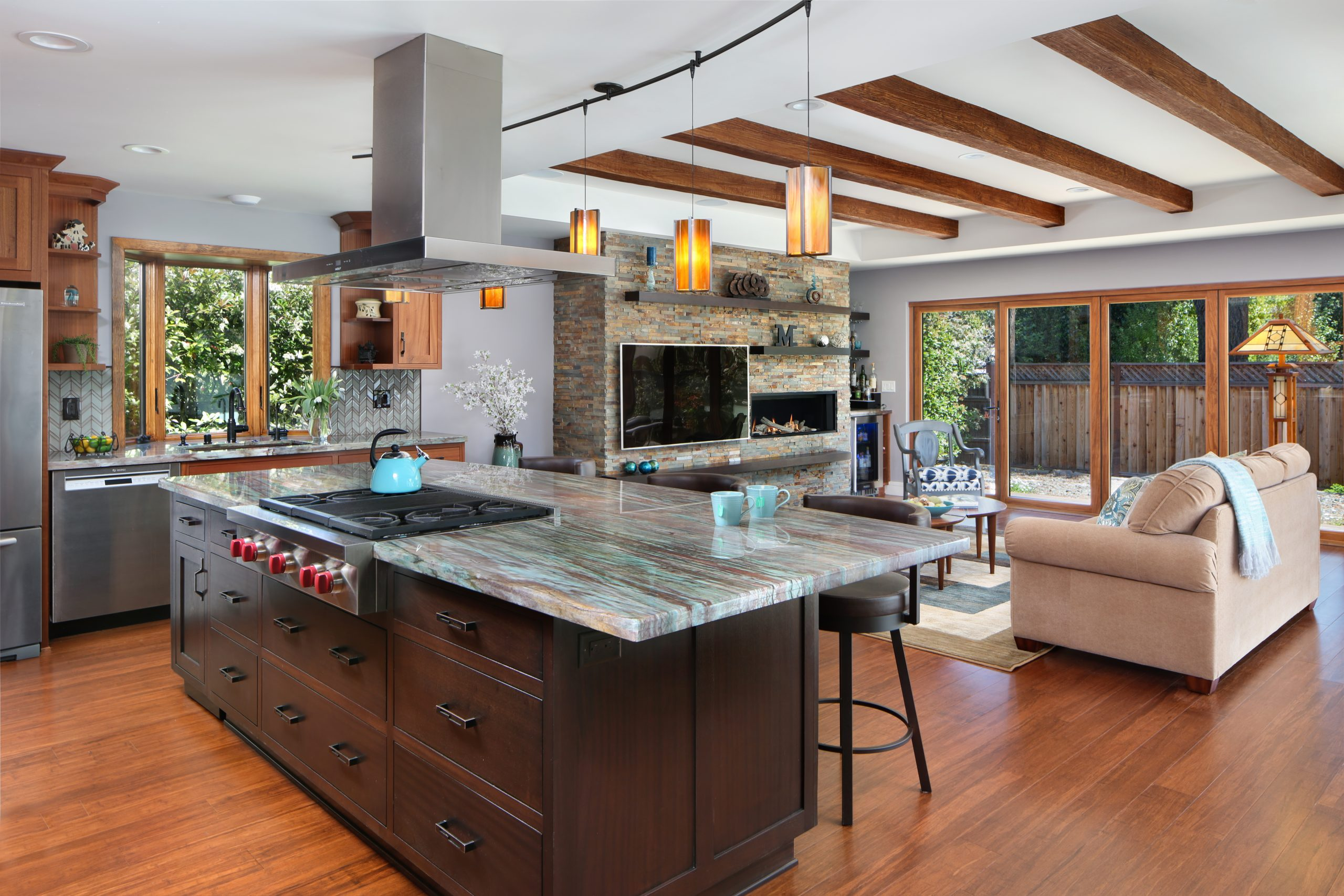A kitchen island with granite counter tops and built in gas stove.
