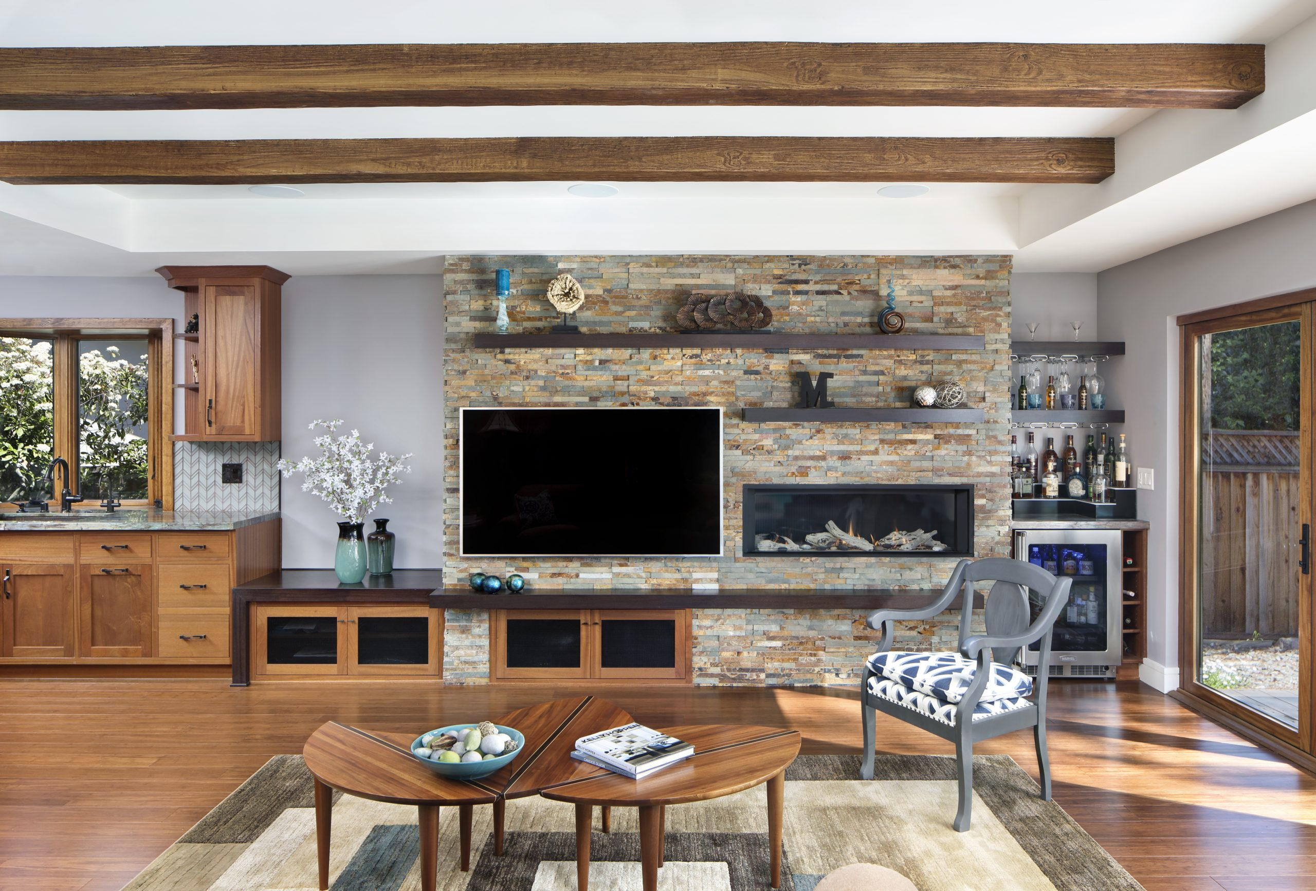 A modern living room with a built in wine refrigerator.