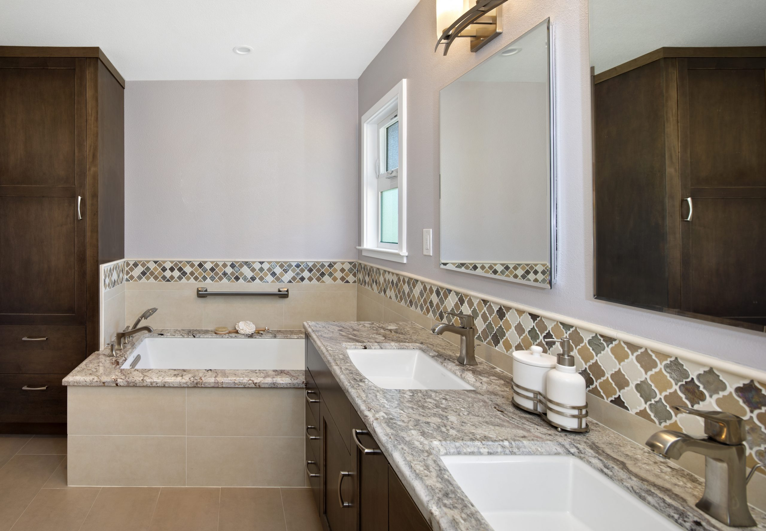 A bathroom with granite counter tops and a granite edged bathtub.