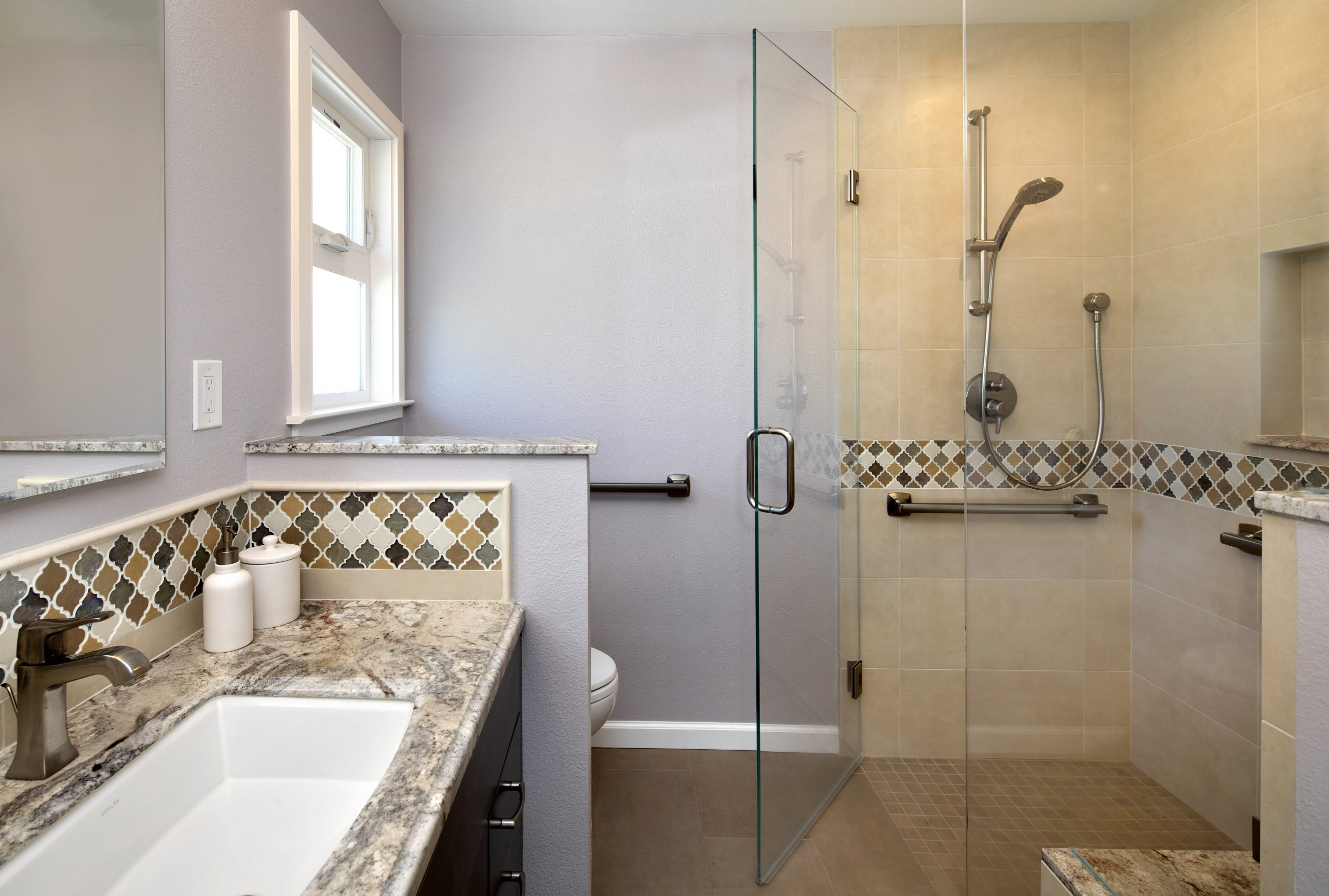 A full glass shower with decorative tile walls.