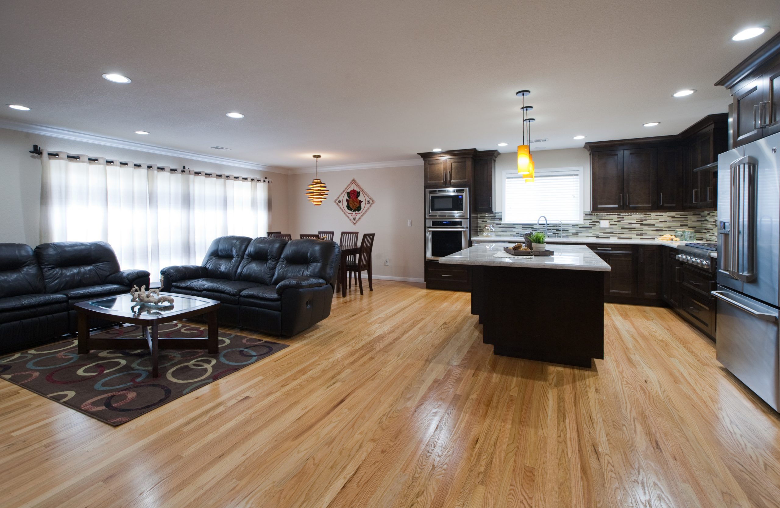 A living room and kitchen remodel with hardwood floors and granite counter tops.