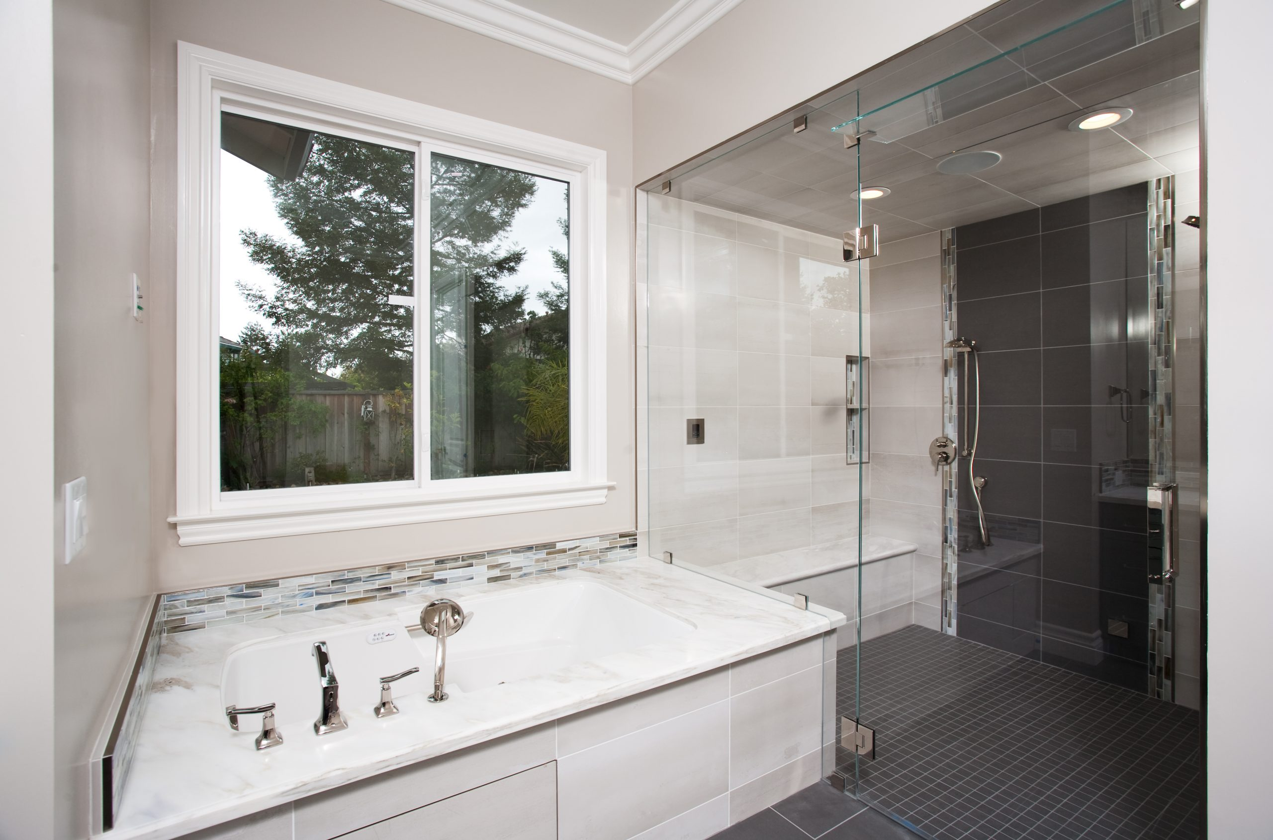 A master bathroom with Jacuzzi tub and large walk in glass shower.
