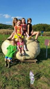 Lots of kids on giant pumpkin