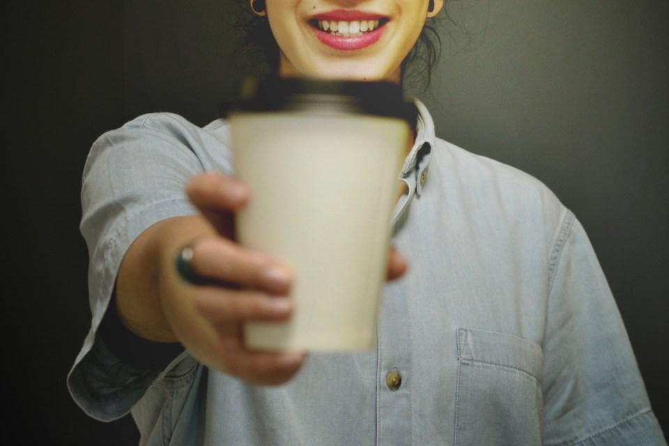 Femme offrant un café avec un sourire