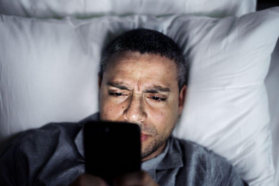 Homme regardant son téléphone durant la nuit