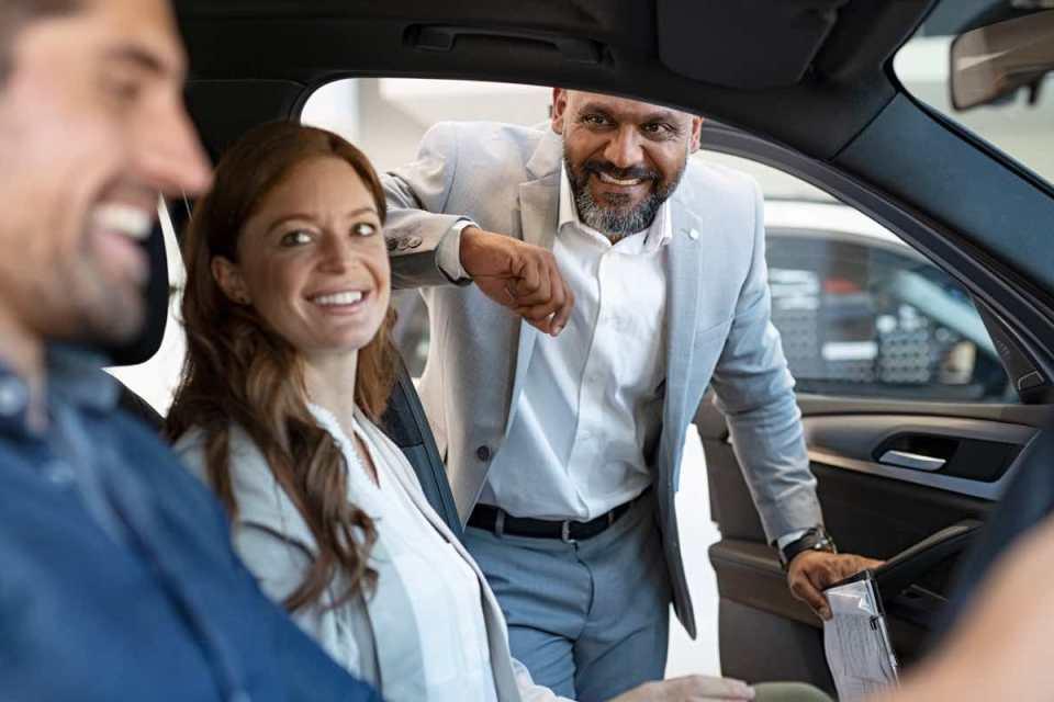 Vendeur de voitures qui discute avec un couple