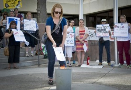 """mkb050815h/metro/Marla Brose/050815 Linnea Montoya, a kindergarten teacher at Montezuma Elementary, drops her teacher evaluation into a waste basket with other burning evaluations in front of Albuquerque Public Schools headquarters, Wednesday, May 20, 2015, in Albuquerque, N.M. A group of teachers filled the entrance to APS to participate in the teacher evaluation protest. """"It insulted my fellow teachers who mentored me and scored lower,"""" Montoya said. (Marla Brose/Albuquerque Journal)"""